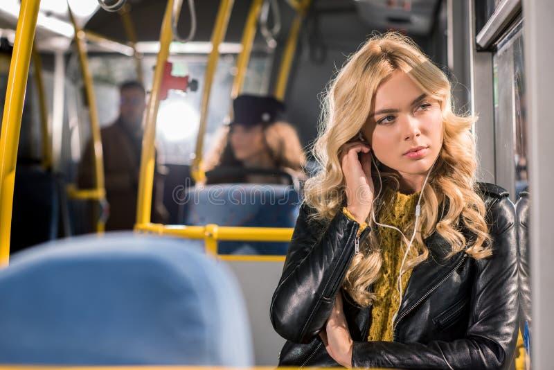 eftertänksam blond flicka i hörlurar som ser fönstret arkivfoto