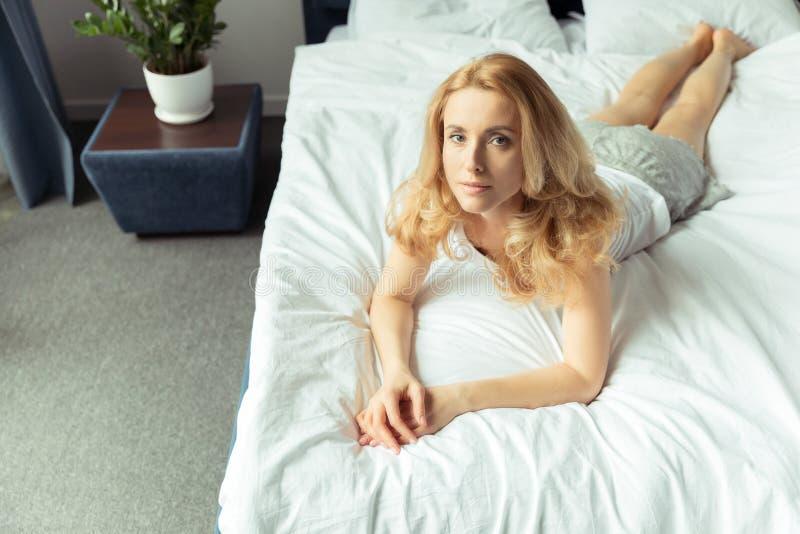 Eftertänksam blond kvinna som hemma ligger på säng fotografering för bildbyråer