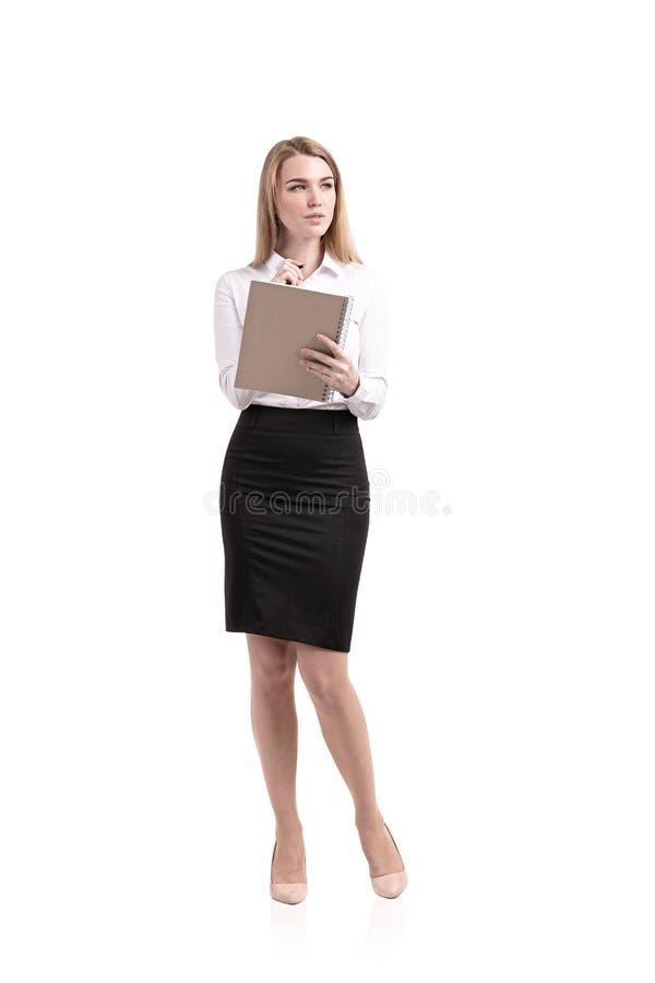 Eftertänksam blond kvinna som skriver i förskriftsboken som isoleras arkivfoto