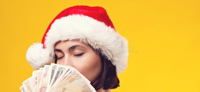 Eftertänksam brunettkvinna i julhatten som rymmer pengar Flicka som drömmer i jul Isolerat på gul bakgrund, kopieringsutrymme royaltyfria bilder