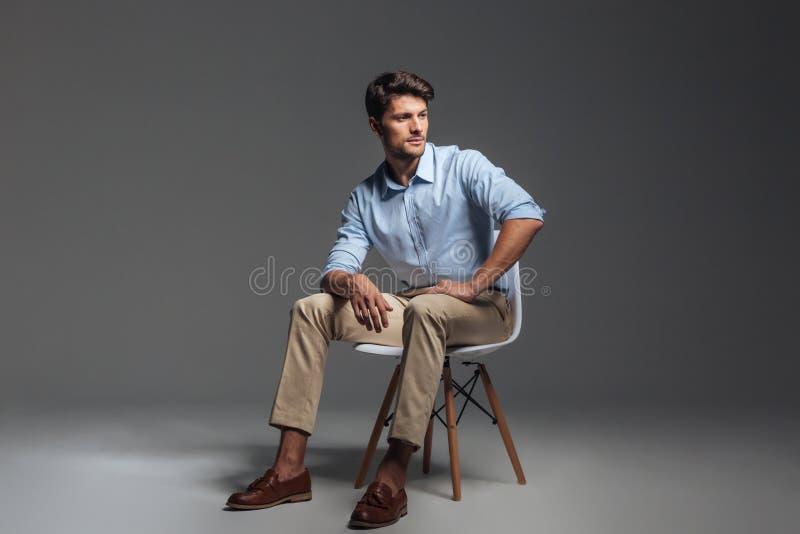 Eftertänksam brunettman i blått skjortasammanträde på stolen royaltyfria foton