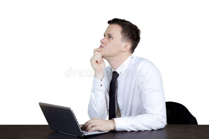 Eftertänksam Caucasian businessperson med bärbara datorn arkivfoto