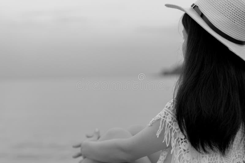 Eftertänksam ensam ung asiatisk kvinna Sidosikten av kvinnan med ledsen känsla i svartvit plats sitter vid havet Tryckt ned och s royaltyfri foto