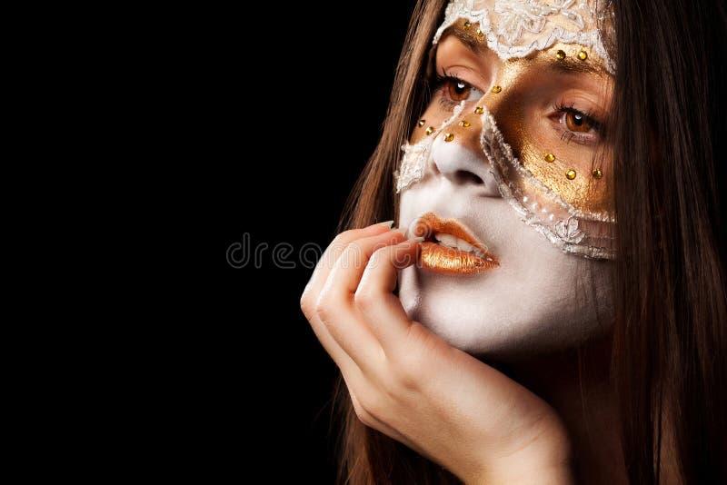 Eftertänksam flicka för framsida i en maskering arkivfoto