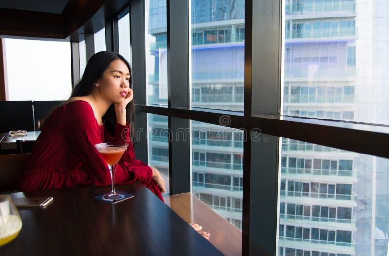 Eftertänksam flicka som har en drink i en stång royaltyfria bilder