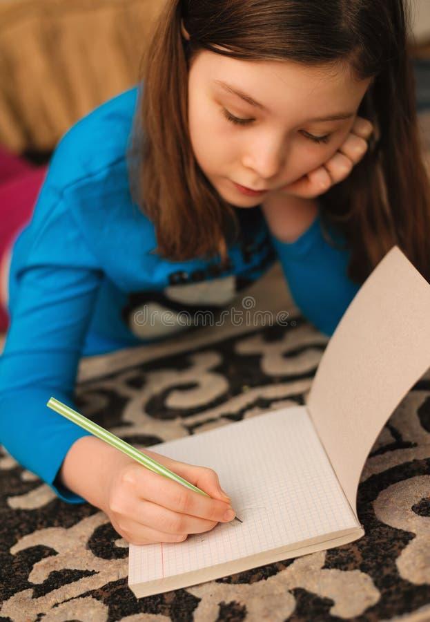 Eftertänksam flicka som ligger på golv och drar blyertspennan royaltyfri fotografi