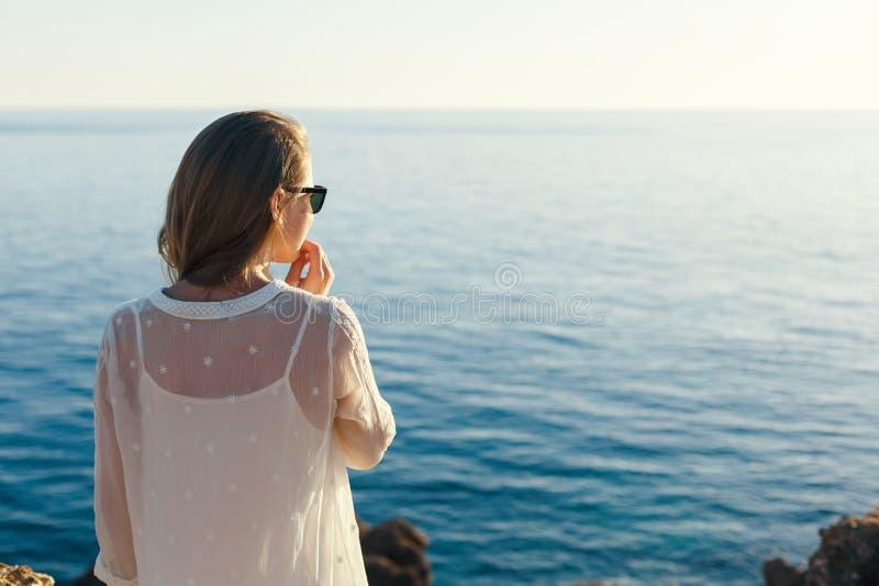 Eftertänksam flicka som ser havssolnedgången royaltyfria foton