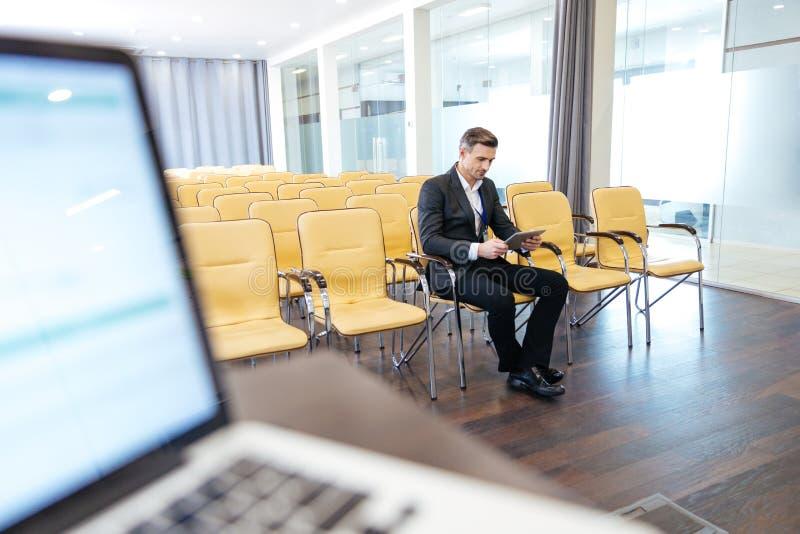 Eftertänksam fokuserad affärsman som använder minnestavlan i tom konferenskorridor royaltyfri fotografi
