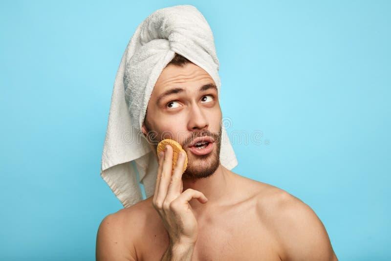 Eftertänksam fundersam stilig man med fuktighetsbevarande hudkräm som ser upp royaltyfri bild