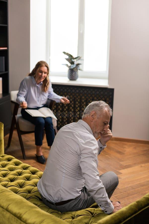 Eftertänksam grå färg-haired man som tyst sitter på soffan arkivfoton