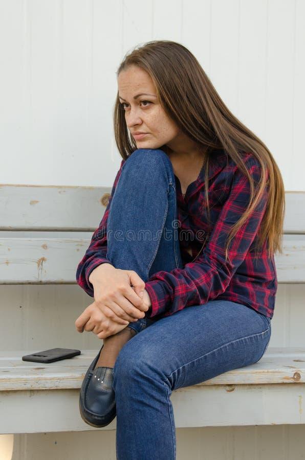 Eftertänksam härlig flicka med långt hår och en röd och blå rutig en skjorta och jeans som sitter på bänk royaltyfri fotografi