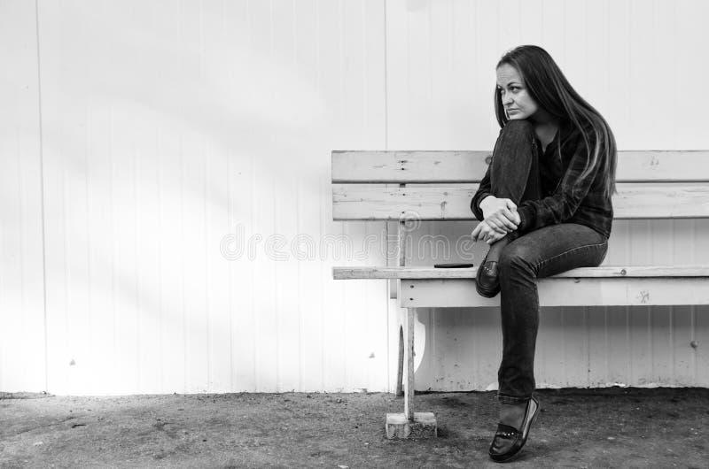 Eftertänksam härlig flicka med långt hår som sitter på bänk royaltyfri fotografi