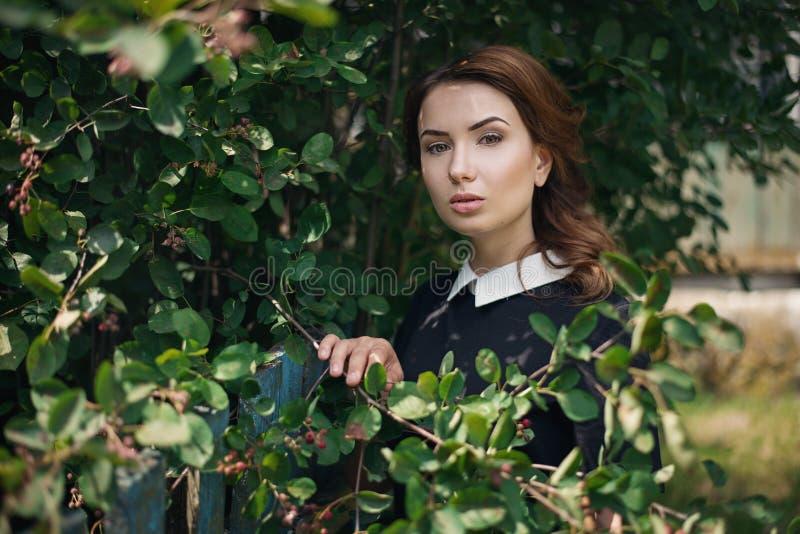 Eftertänksam härlig ung flicka i retro stilklänninganseende i trädgården nära staketet kvinna för closeupframsidastående Hon är e royaltyfri bild