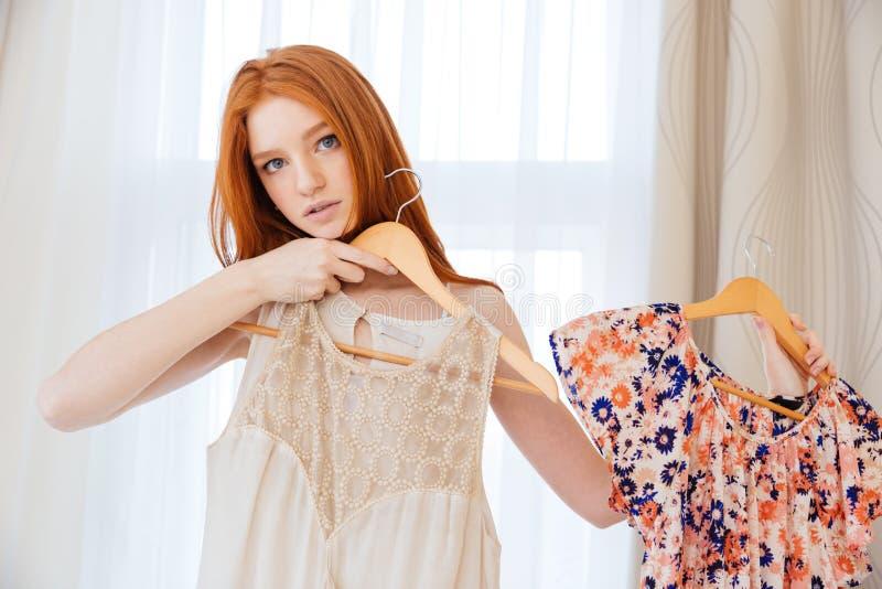 Eftertänksam härlig ung kvinna som desiding vad för att bära arkivfoton
