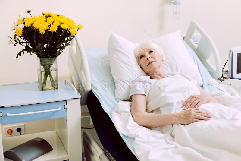 Eftertänksam hög dam som ligger i sjukhussäng arkivfoton