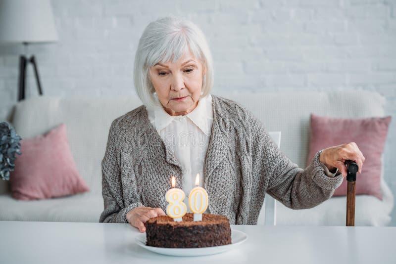 eftertänksam hög dam som sitter på tabellen med födelsedagkakan med stearinljus bara arkivbilder