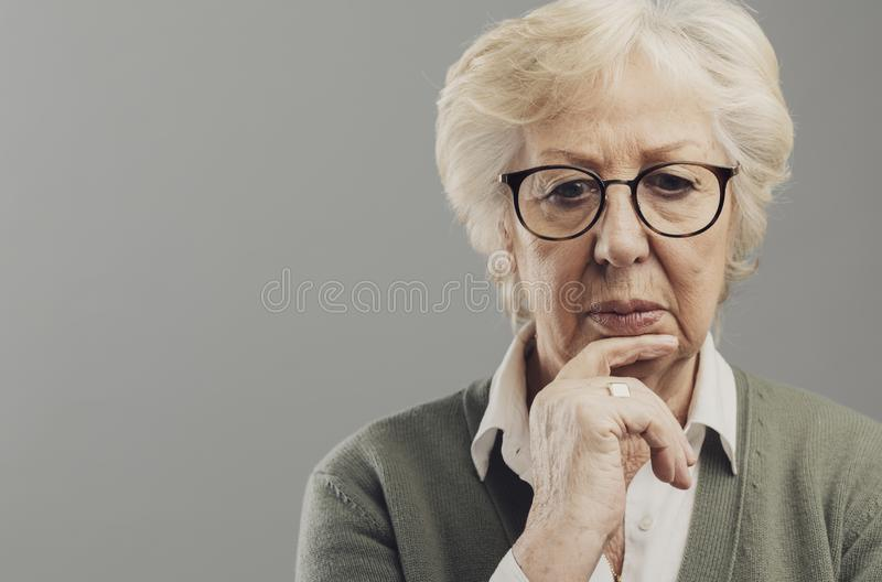 Eftertänksam hög kvinna som tänker med handen på hakan royaltyfria bilder