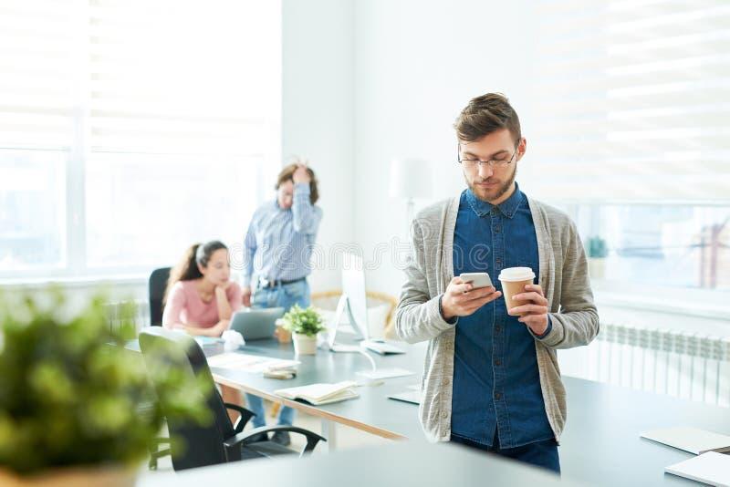 Eftertänksam hipsterkrubba som dricker kaffe i mötesrum royaltyfria foton
