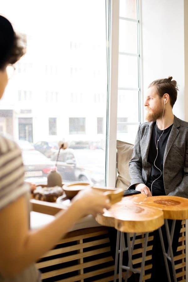 Eftertänksam hipsterman som ut ser fönstret i kafé arkivfoto