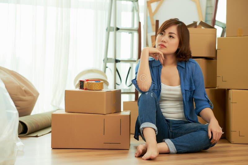 Eftertänksam kvinna som distraheras från emballagematerial royaltyfri foto