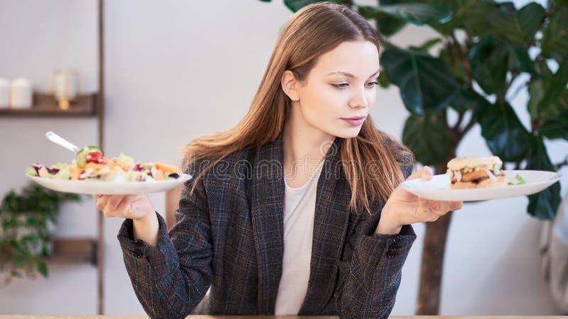 Eftertänksam kvinna som gör beslut mellan sund mat och snabbmat ?ta f?r begrepp som ?r sunt Aff?rskvinna i en kl? upp fotografering för bildbyråer