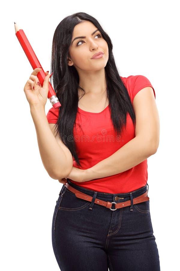 Eftertänksam kvinna som rymmer en enorm blyertspenna royaltyfria foton
