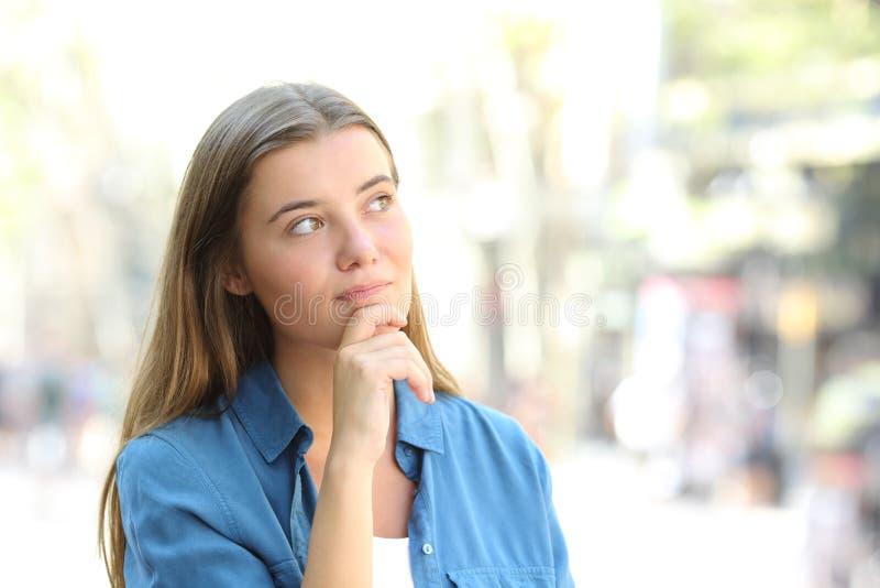 Eftertänksam kvinna som ser sidan i gatan arkivfoto