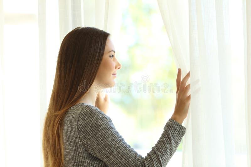 Eftertänksam kvinna som ser till och med ett fönster royaltyfria foton