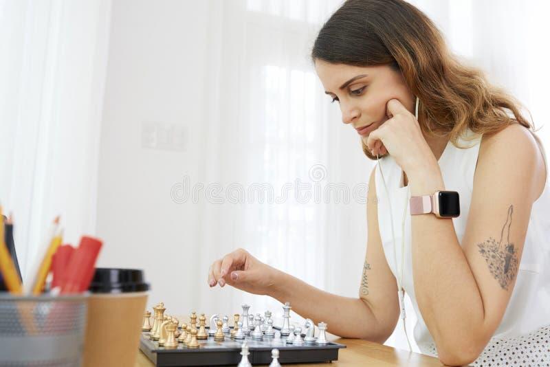 Eftertänksam kvinna som spelar schack royaltyfri fotografi