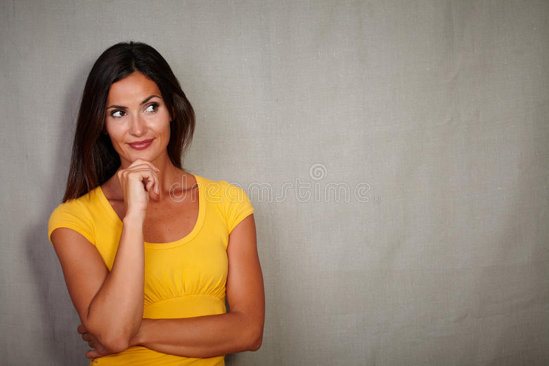 Eftertänksam kvinna som tänker med handen på hakagest royaltyfri foto