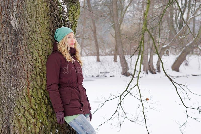 Eftertänksam kvinnabenägenhet mot träd i vinter royaltyfri foto