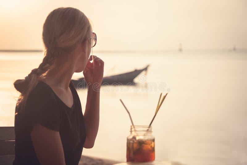 Eftertänksam kvinnaturist på stranden under ferier som ser in i avståndet in mot horizont- och solnedgånghimmel arkivbild