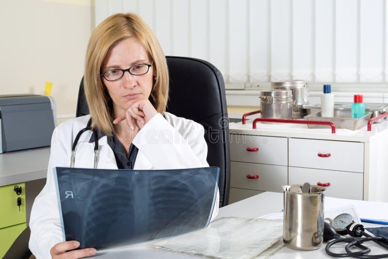 Eftertänksam kvinnlig doktor Looking på patients lungaröntgenstrålen i konsulterande rum royaltyfria foton
