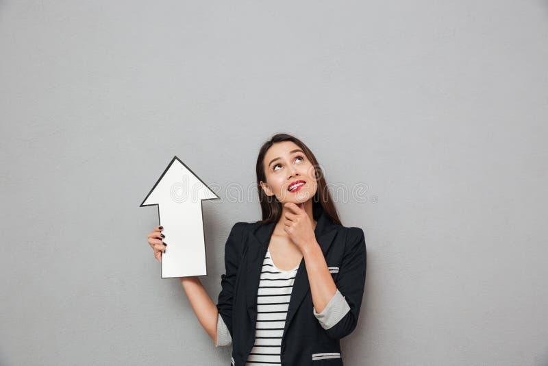 Eftertänksam le asiatisk affärskvinna som pekar med den pappers- pilen arkivfoton