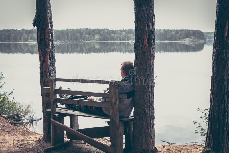 Eftertänksam man på den höga kanten av sammanträde för flodbank på bänken och att se på härligt landskap med stillsamt vatten fotografering för bildbyråer