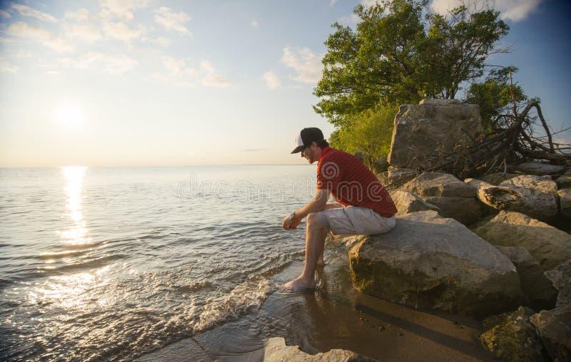 Eftertänksam man som placerar vid en sjö royaltyfri bild