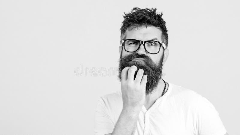 Eftertänksam man som trycker på hans skägg på den vita väggen Den stiliga mannen i exponeringsglas tänker Den emotionella skäggig royaltyfria bilder