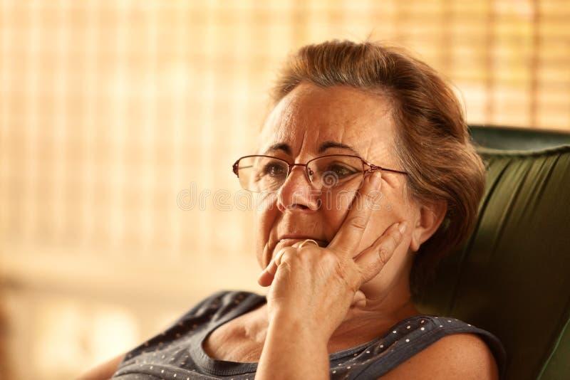 Eftertänksam mogen kvinna arkivfoton