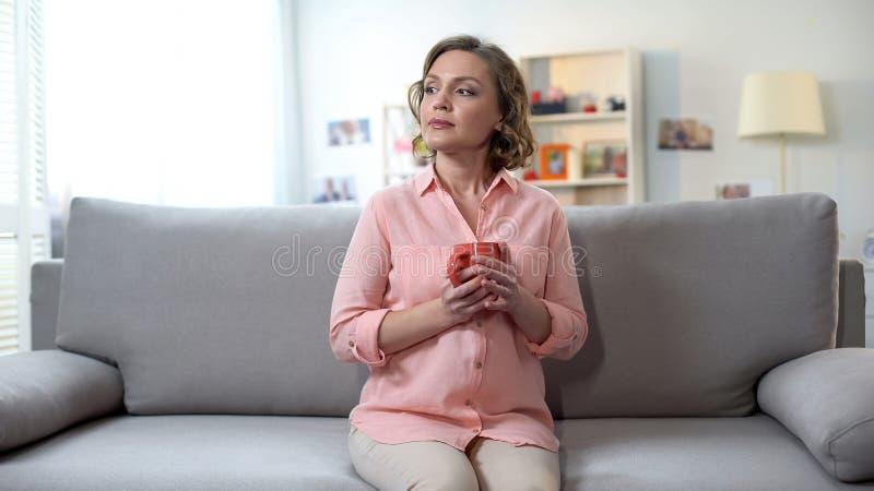 Eftertänksam nätt kvinna som sitter på soffan med kopp te som tänker om problem royaltyfria bilder