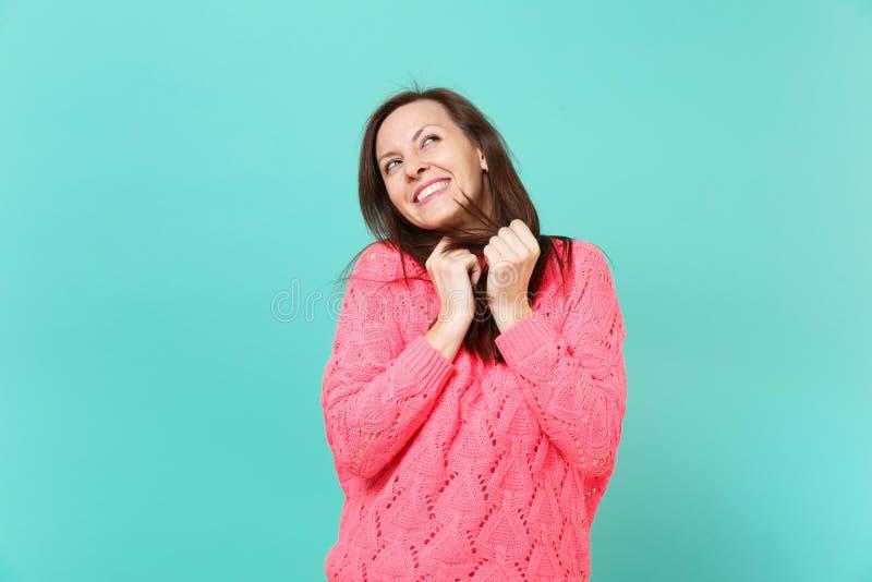 Eftertänksam nätt ung kvinna i den stack rosa tröjan som ser upp, drömma som isoleras på blå turkosväggbakgrund royaltyfri bild