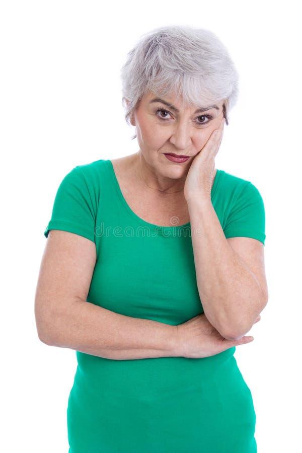 Eftertänksam och ledsen äldre kvinna som isoleras på vit. royaltyfri fotografi