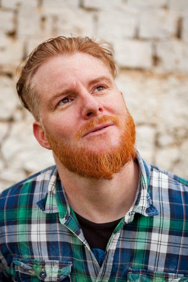 Eftertänksam röd haired hipsterman med den blåa plädskjortan royaltyfria bilder
