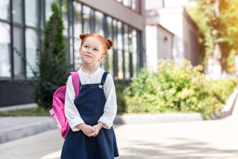 eftertänksam röd haired skolflicka i anblickar som bär ryggsäcken royaltyfria bilder