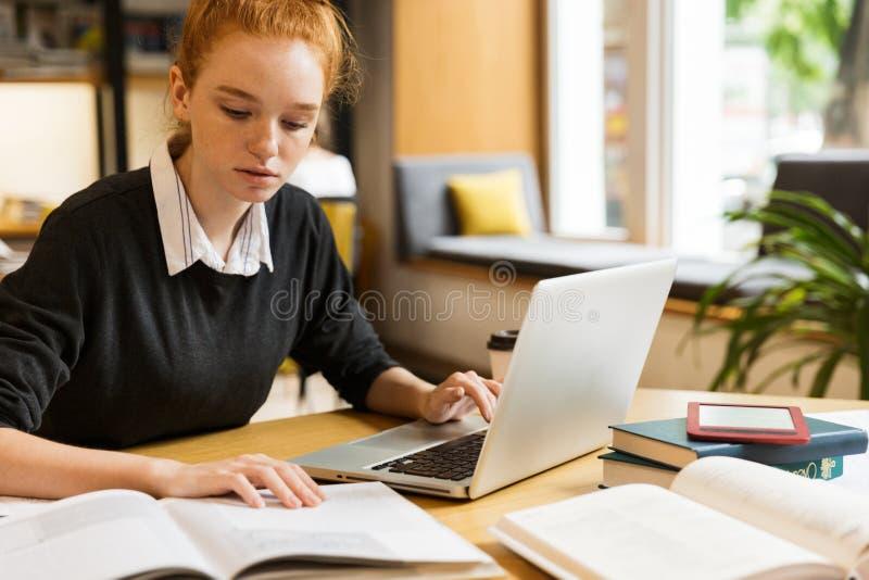 Eftertänksam röd haired tonårs- flicka som använder bärbar datordatoren royaltyfri fotografi