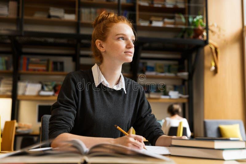 Eftertänksam röd haired tonårs- flicka som studerar på tabellen royaltyfria bilder
