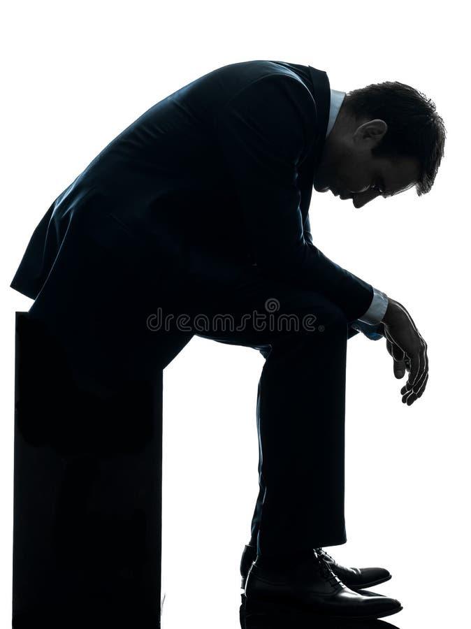Eftertänksam silhouette för ledset affärsmansammanträde royaltyfri foto
