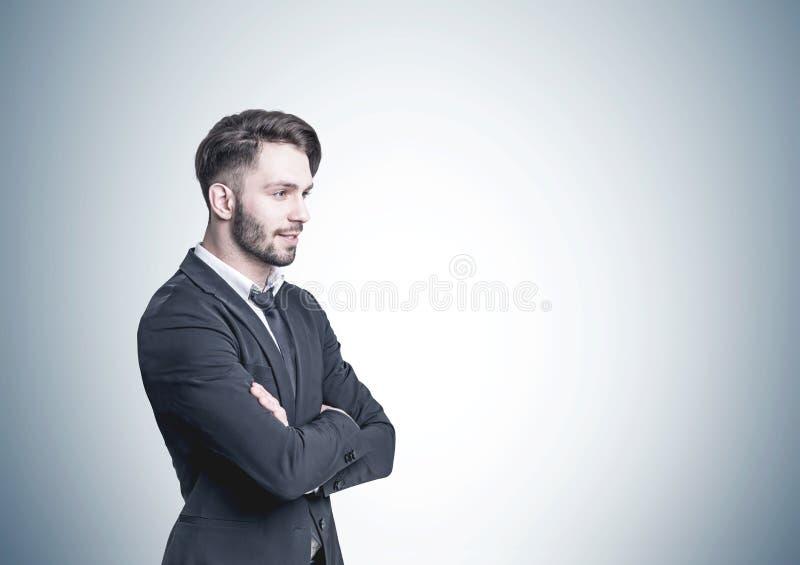 Eftertänksam skäggig affärsman, sidosikt, grå vägg arkivfoton