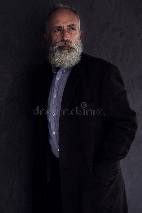 Eftertänksam skäggig man som någonstans ser, medan posera i mörk studi royaltyfri foto