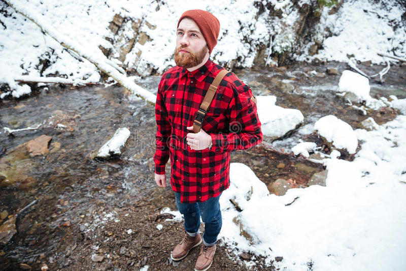 Eftertänksam skäggig ung man som står den near bergfloden i vinter royaltyfri fotografi
