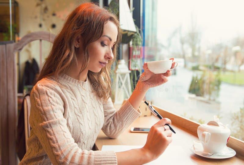 Eftertänksam student som studerar och lär ta anmärkningar som dricker te i en coffee shop arkivbilder